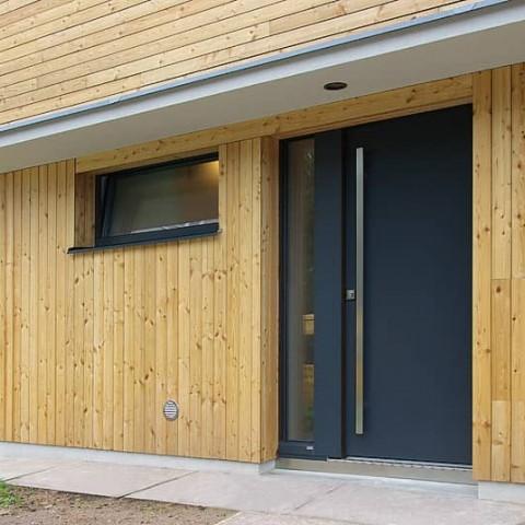 Vchodové dveře PROGRESSION v dřevěné fasádě